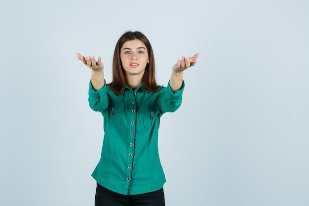 Junge frau im grünen hemd, das einlädt, zu kommen und aufgeregt, vorderansicht zu schauen.