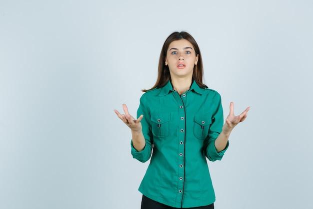 Junge frau im grünen hemd, das hände auf aggressive weise anhebt und schockiert, vorderansicht schaut.