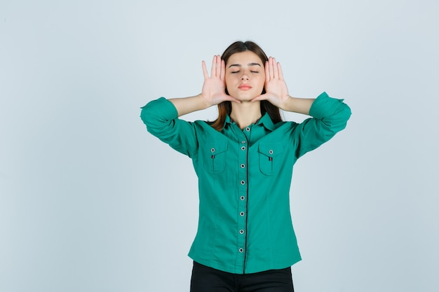 Junge frau im grünen hemd, das mit den händen auf den seiten des gesichts aufwirft und entspannt, vorderansicht schaut.