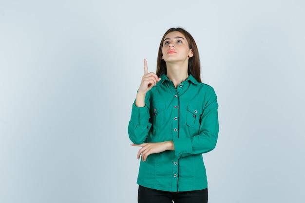 Junge frau im grünen hemd, das oben zeigt und hoffnungsvoll, vorderansicht schaut.