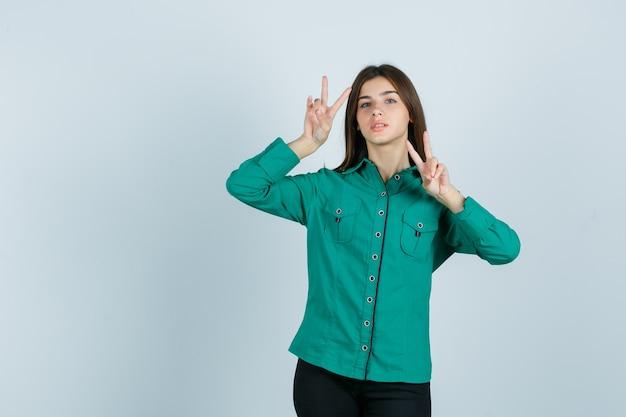 Junge frau im grünen hemd, das siegeszeichen zeigt und zuversichtlich, vorderansicht schaut.
