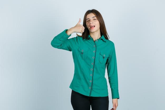 Junge frau im grünen hemd, hose, die daumen oben zeigt, während sie blinkt und selbstbewusst aussieht, vorderansicht.