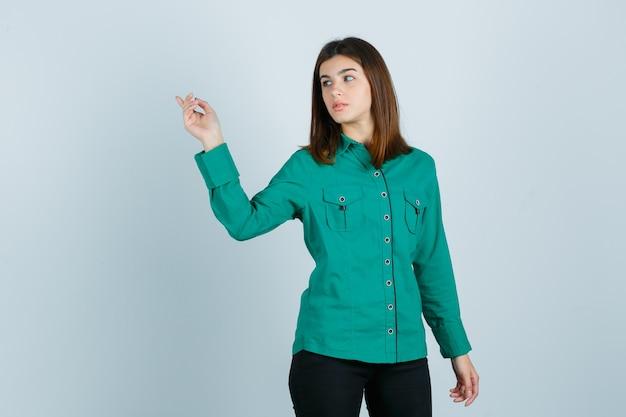 Junge frau im grünen hemd, hose zeigt auf obere linke ecke und schaut fokussiert, vorderansicht.