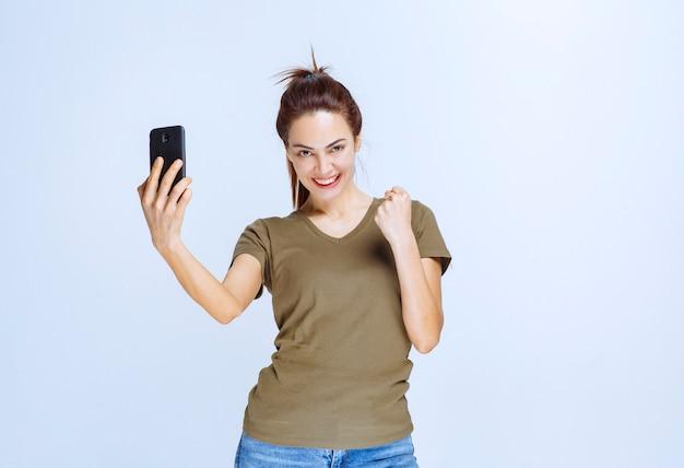 Junge frau im grünen hemd macht ihr selfie und sieht motiviert aus