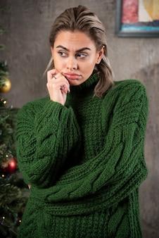 Junge frau im grünen pullover, der weg schaut und aufwirft