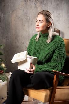 Junge frau im grünen pullover sitzend und posierend mit einer geschenkbox