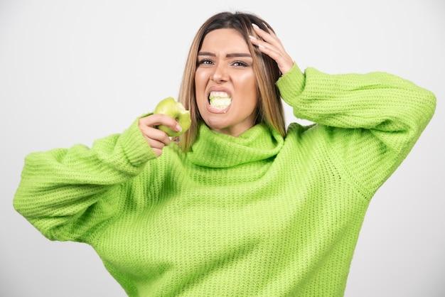 Junge frau im grünen t-shirt, das einen apfel isst