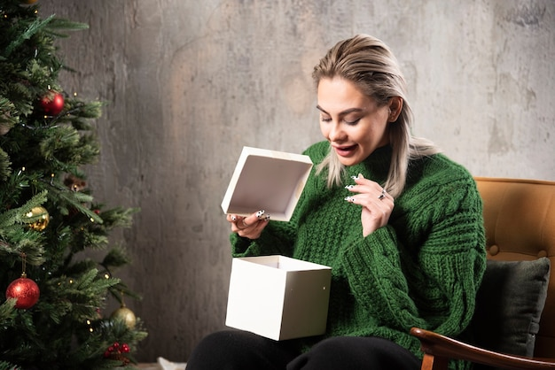 Junge frau im grünen warmen pullover aufgeregt über ein geschenk