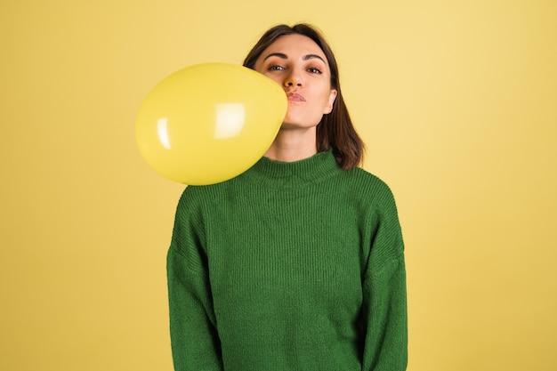 Junge frau im grünen warmen pullover bläst luftballon