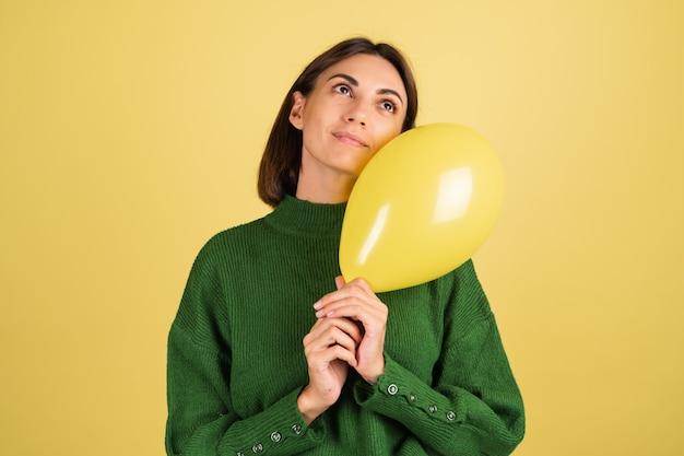 Junge frau im grünen warmen pullover lächelnd mit luftballon