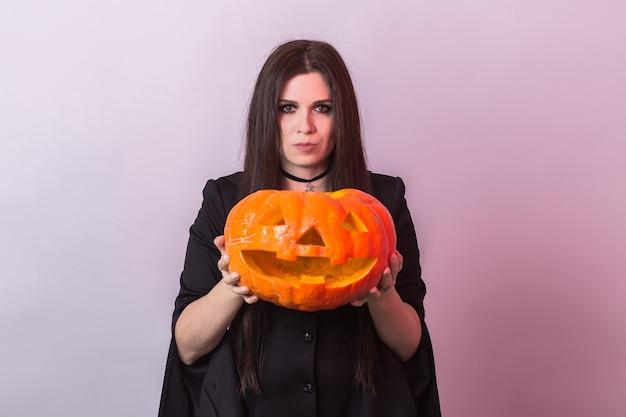 Junge frau im halloween-hexenkostüm im studio mit gelbem kürbis.