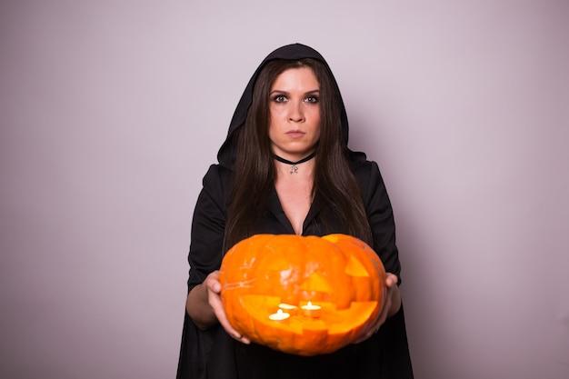 Junge frau im halloween-hexenkostüm mit gelbem kürbis.