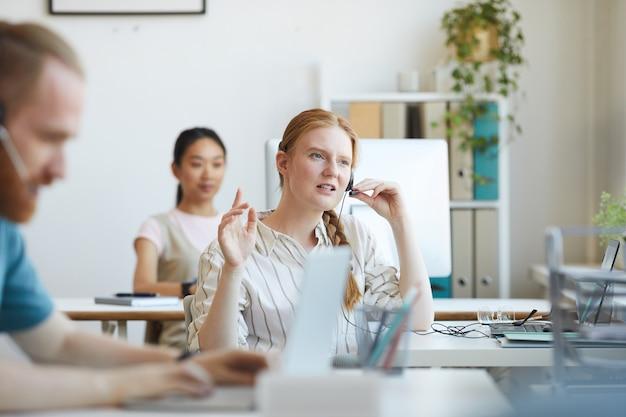 Junge frau im headset sitzt an ihrem arbeitsplatz im büro und berät den kunden am telefon