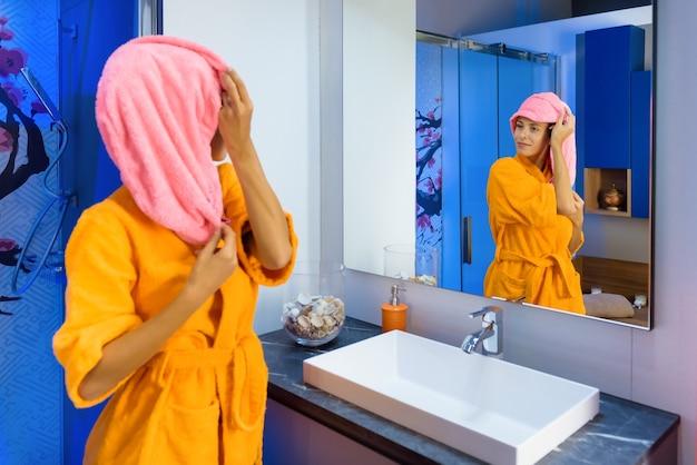 Junge frau im hellen bademantel, der sich im spiegel betrachtet