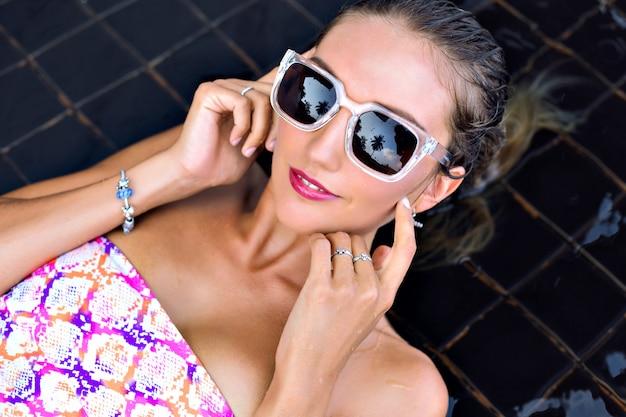 Junge frau im hellen bikini und in der stilvollen sonnenbrille, am kreativen schwarzen pool gelegen und entspannt, genießen sie ihren urlaub.