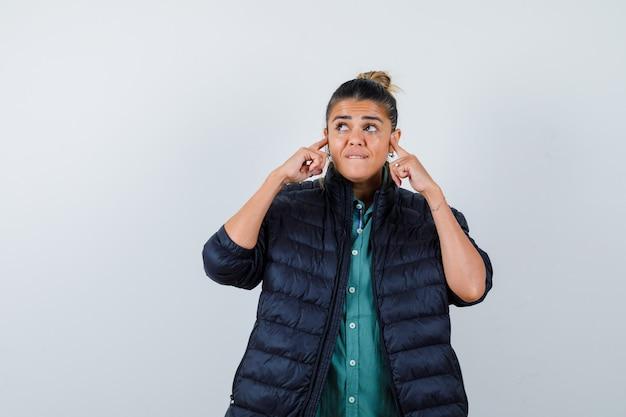 Junge frau im hemd, pufferjacke, die ohren mit den fingern verstopft, lippe beißt, aufschaut und beunruhigt aussieht, vorderansicht.