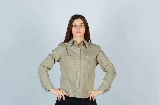 Junge frau im hemd, rock hält die hände auf den hüften und sieht selbstbewusst aus, vorderansicht.