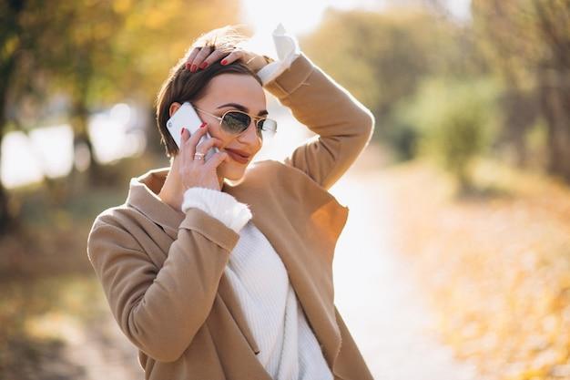 Junge frau im herbstpark unter verwendung des telefons