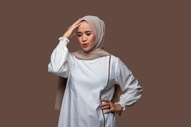 Junge frau im hijab, die den kopf mit schwindligen ausdrucksstresskopfschmerzen hält