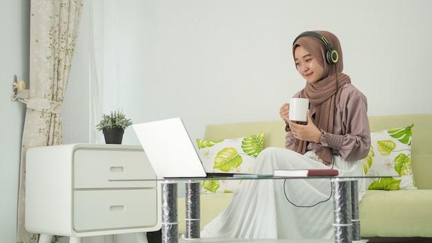 Junge frau im hijab, die von zu hause aus arbeitet und einen drink genießt, während sie über kopfhörer hört?