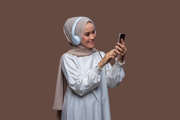 Junge frau im hijab mit weißen kopfhörern beim berühren des telefonbildschirms