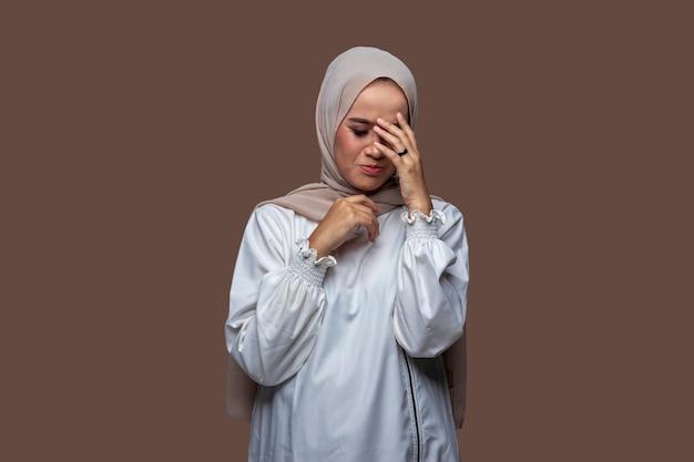 Junge frau im hijab posiert mit schwindligen und traurigen kopfschmerzen