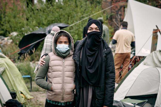 Junge frau im hijab und ihre tochter stehen gegen zeltlager