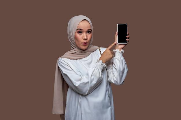 Junge frau im hijab zeigte mit schockiertem gesichtsausdruck auf den handybildschirm