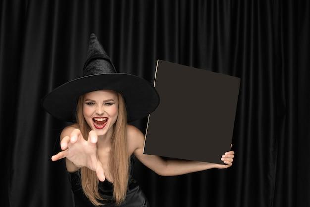 Junge frau im hut als hexe auf schwarzem vorhang