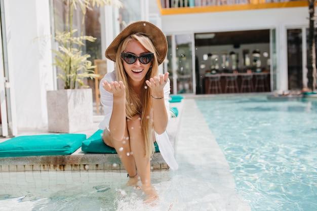 Junge frau im hut, der nahe wasser kühlt und lacht. elegantes weibliches modell im hemd und in den gläsern, die neben pool sitzen.