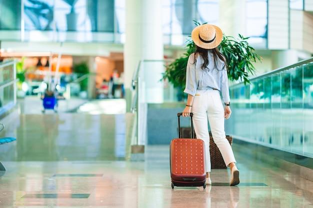 Junge frau im hut mit gepäck im internationalen flughafen, der mit ihrem gepäck geht.