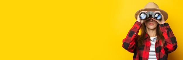 Junge frau im hut und im karierten hemd, die durch fernglas auf gelbem hintergrund schauen.
