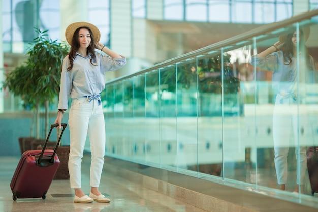 Junge frau im internationalen flughafen mit ihrem gepäck
