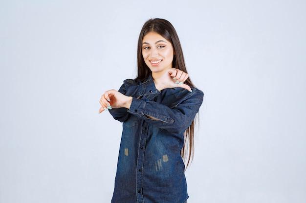 Junge frau im jeanshemd, das daumen unten zeichen zeigt