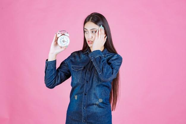 Junge frau im jeanshemd, das den wecker hält und ihr ohr wegen des rings bedeckt