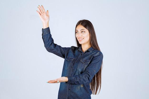 Junge frau im jeanshemd, das die maße eines produktes zeigt