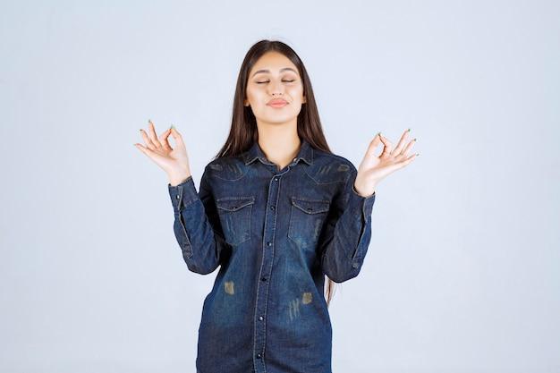 Junge frau im jeanshemd, das genusszeichen zeigt