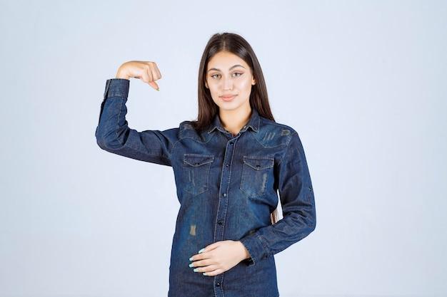 Junge frau im jeanshemd, das ihre armmuskeln zeigt
