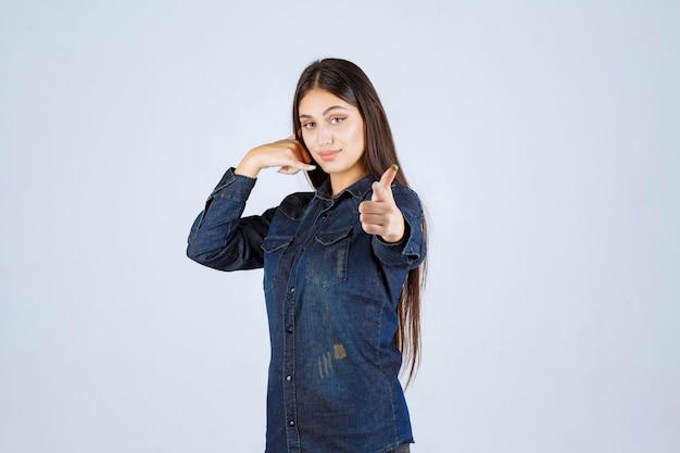 Junge frau im jeanshemd, das rufzeichen zeigt