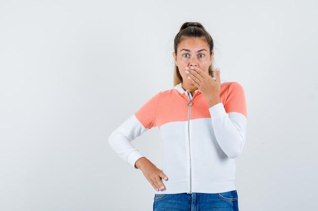 Junge frau im kapuzenpullover mit reißverschluss, jeans, die den mund mit der hand bedecken, hand auf hüfte halten und beschämt aussehen