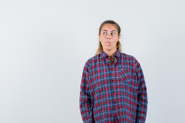 Junge frau im karierten hemd, das gerade steht, zunge herausstreckt und vorne aufwirft und hübsch aussieht