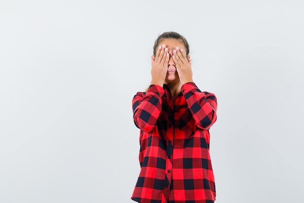 Junge frau im karierten hemd, das hände auf augen hält und ruhige vorderansicht schaut.