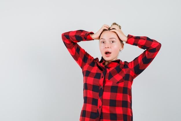 Junge frau im karierten hemd, das hände auf kopf hält und munter aussieht