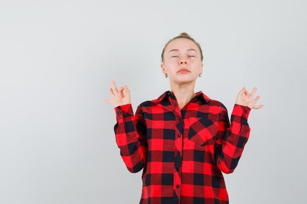 Junge frau im karierten hemd, das meditation mit geschlossenen augen tut und entspannt, vorderansicht schaut.