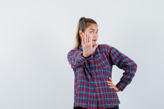 Junge frau im karierten hemd, das stoppschild zeigt, während hand auf taille hält und hübsch aussieht