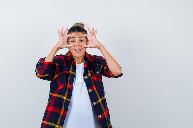 Junge frau im karierten hemd, die augen mit den fingern öffnet und lustig schaut, vorderansicht.