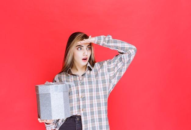 Junge frau im karierten hemd hält eine silberne geschenkbox und sieht verängstigt und verängstigt aus