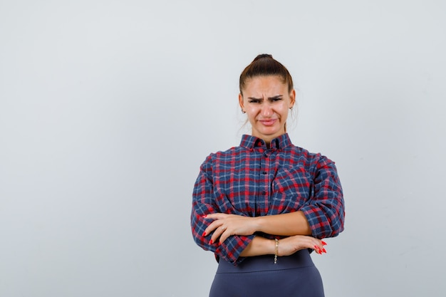 Junge frau im karierten hemd, hose, die mit verschränkten armen steht und unzufrieden aussieht, vorderansicht.