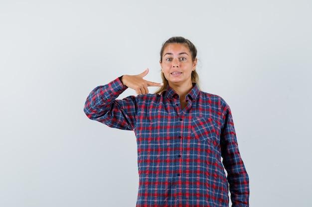 Junge frau im karierten hemd zeigt auf sich selbst und sieht hübsch aus