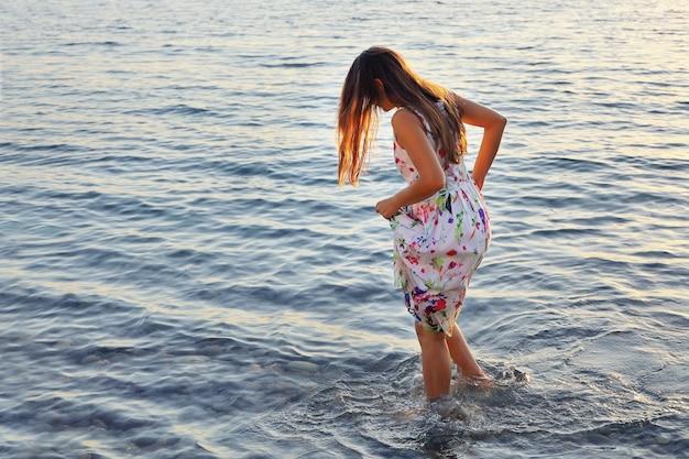 Junge frau im kleid geht langsam barfuß auf wasser bei sonnenuntergang am sommertag